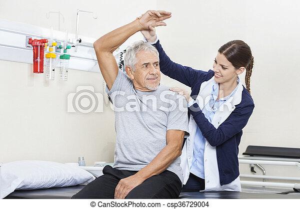 Physiotherapist Assisting Senior Man To Exercise - csp36729004
