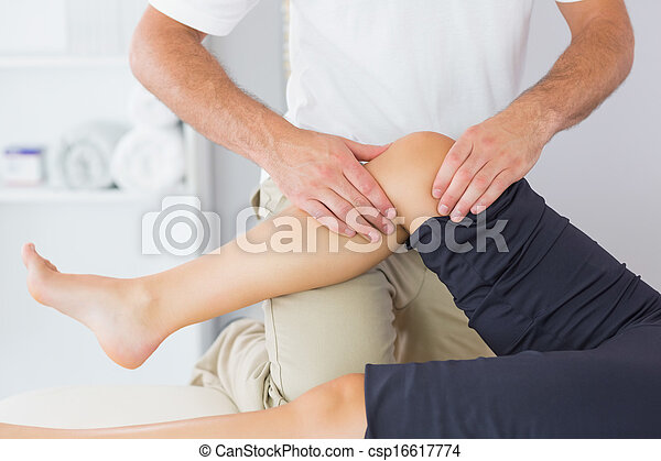 Physiotherapist controlling knee of a patient - csp16617774