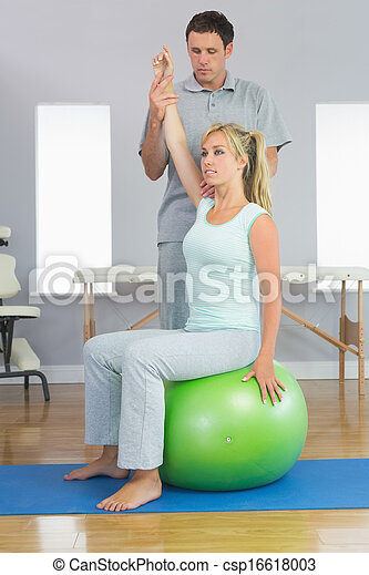 Physiotherapist correcting patient sitting on exercise ball - csp16618003