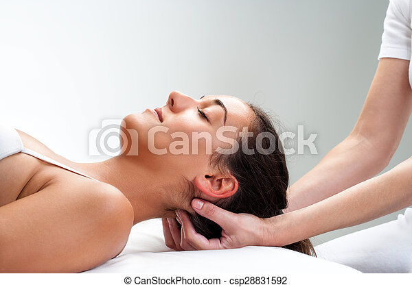 Physiotherapist pressing back of womans head. - csp28831592