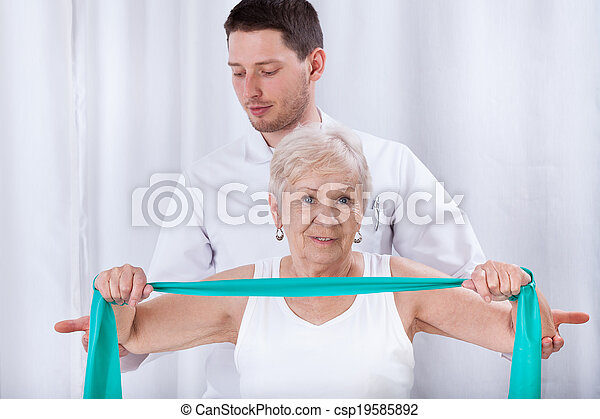 Physiotheraqpist assisting elderly woman in exercising - csp19585892