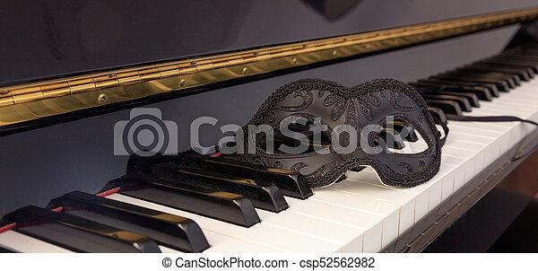 Máscara de carnaval en el teclado de piano clásico - csp52562982
