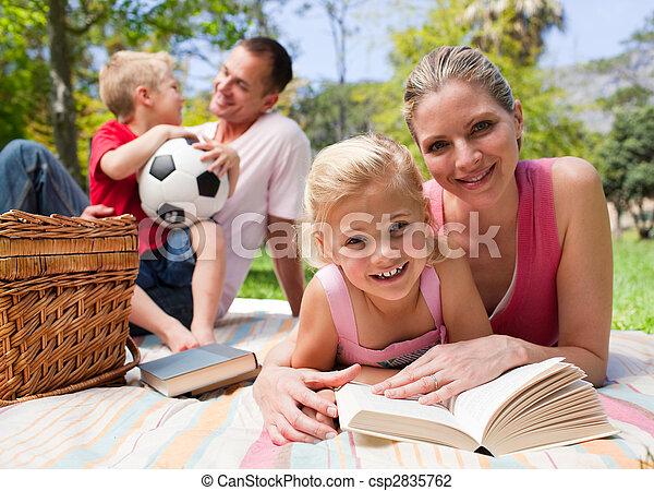 Una joven familia feliz disfrutando de un picnic - csp2835762