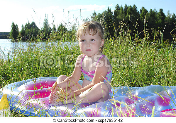 Picnic. Little girl sitting on the grass near the lake  - csp17935142