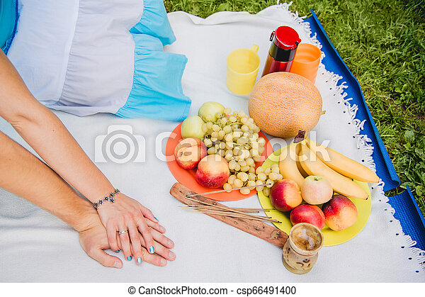Picnic time. Young couple eating grapes and enjoying in picnic. Love and tenderness, dating, romance, lifestyle concept - csp66491400