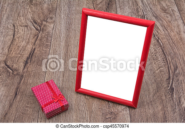 Picture frame with a gift on a wooden background - csp45570974