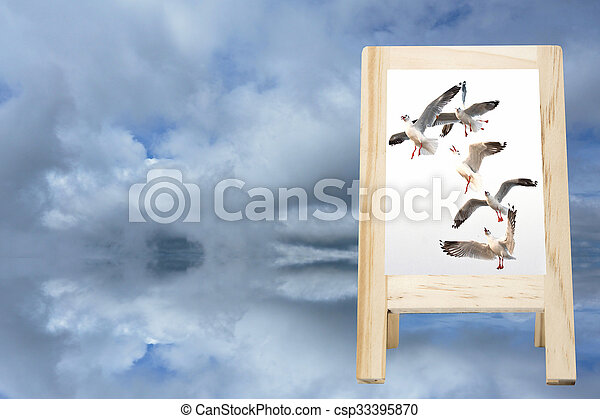 Picture frames, wooden bird blur the background sky