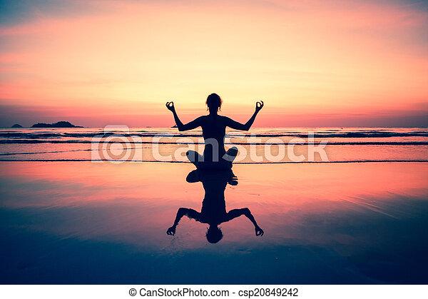 Yoga mujer sentada en la costa del mar al atardecer, con colores de imágenes en surrealistas. - csp20849242
