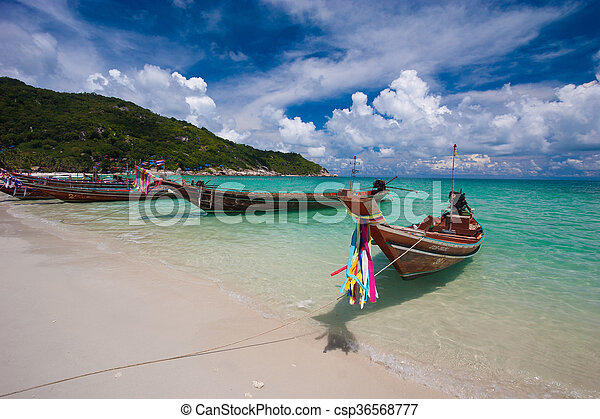 Picture of empty long tail boat on tropical beach. Clear water and blue sky with clouds. Horizontal - csp36568777