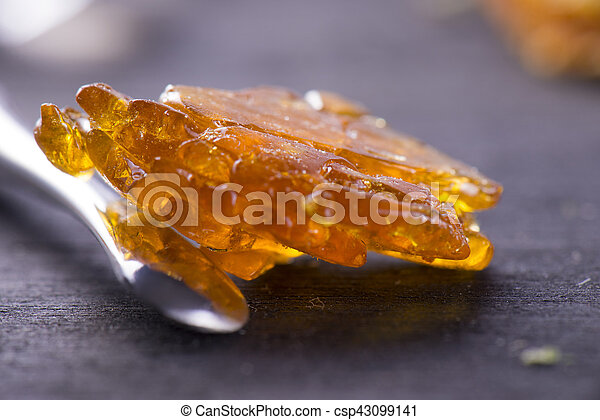 Piece of cannabis oil concentrate aka shatter with dabbing tool - csp43099141