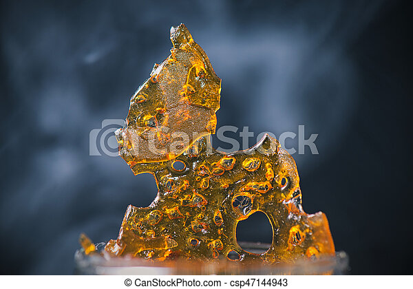 Piece of cannabis oil concentrate aka shatter with smoke - csp47144943