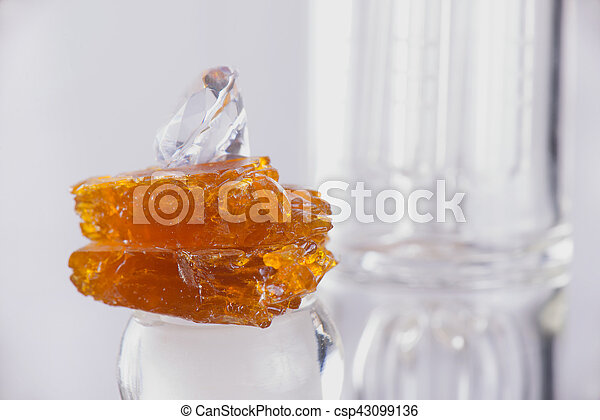 Piece of cannabis oil concentrate aka shatter over a glass rig isolated - csp43099136