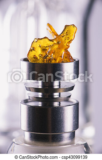 Piece of cannabis oil concentrate aka shatter over a titanium rig bowl isolated - csp43099139