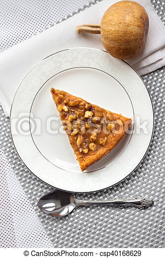 Piece of pumpkin pie with walnuts on a plate - csp40168629