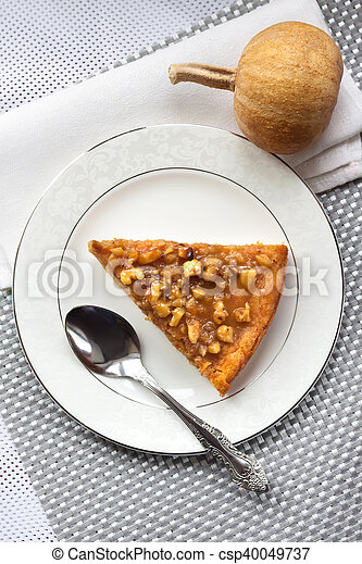 Piece of pumpkin pie with walnuts on a plate - csp40049737