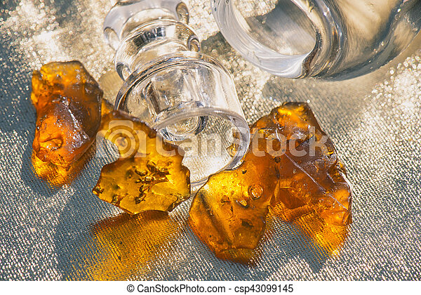 Pieces of cannabis oil concentrate aka shatter with glass rig - csp43099145