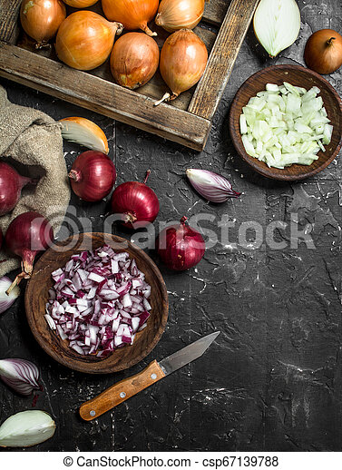 Pieces of onions in a bowl with a yellow onion on tray and red onion in a sack. - csp67139788