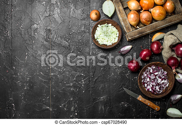 Pieces of onions in a bowl with a yellow onion on tray and red onion in a sack. - csp67028490