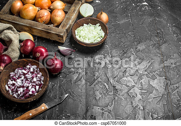 Pieces of onions in a bowl with a yellow onion on tray and red onion in a sack. - csp67051000