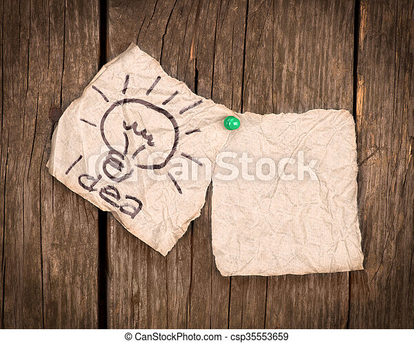 pieces of paper with the word idea on a wooden background - csp35553659