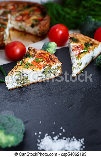 pieces of vegetable pie with cottage cheese, tomatoes, dill and asparagus beans on a dark ceramic background. - csp54062193