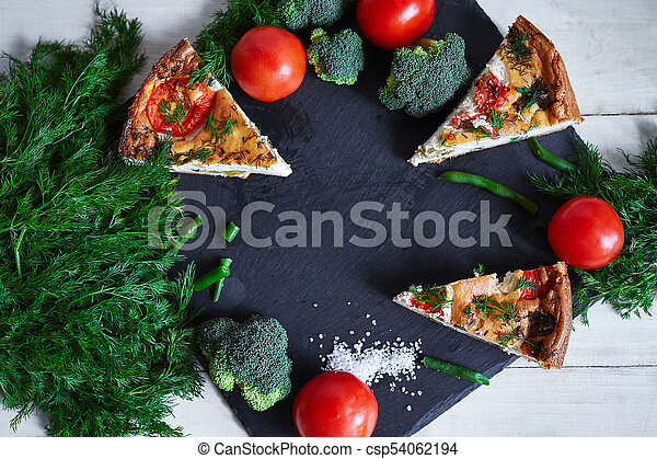 pieces of vegetable pie with cottage cheese, tomatoes, dill and asparagus beans on a dark ceramic background. - csp54062194