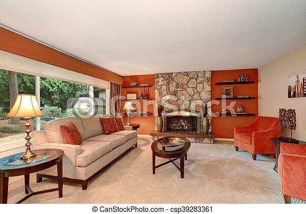 Acogedor salón familiar en tonos rojos con chimenea de piedra. - csp39283361