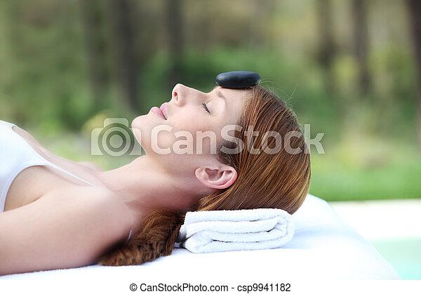 Una mujer tumbada en una cama de masaje con piedra caliente en la frente - csp9941182