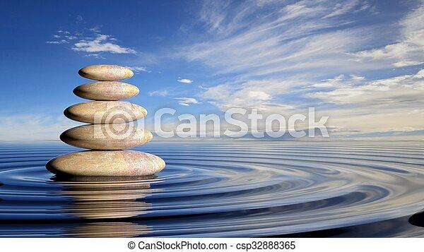 Las piedras Zen se amontonan de grandes a pequeñas en agua con ondas circulares y cielo pacífico. - csp32888365