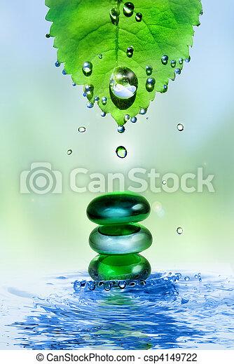 Balanceando piedras brillantes en agua salpicando con hojas y gotas - csp4149722