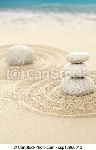 Piedras zen balanceadas en arena con mar en el fondo - csp13966013