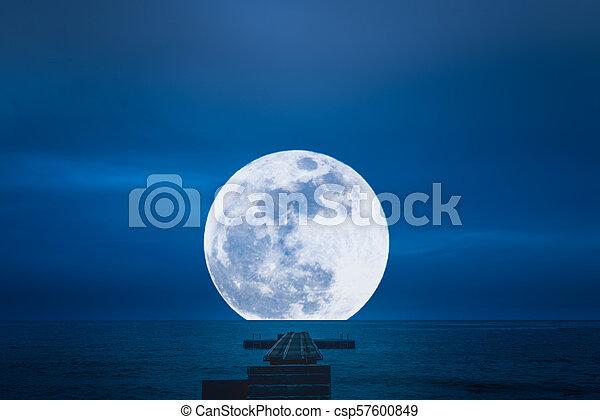 Pier into the full moon - csp57600849