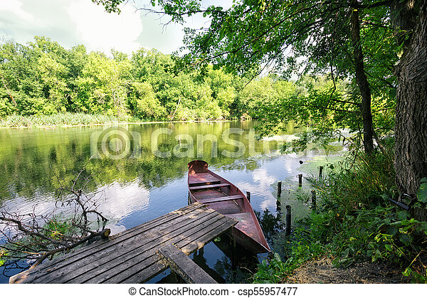 Pier with red boat on the river bank - csp55957477