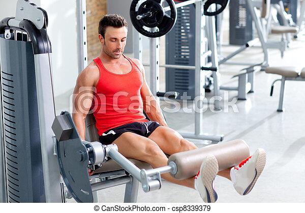 Hombre levantando pesas con una pierna de prensa en el gimnasio deportivo - csp8339379
