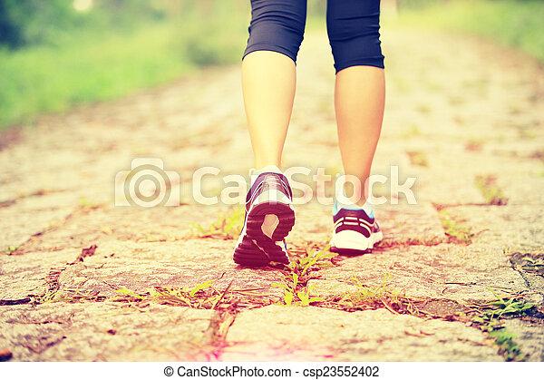 Piernas de mujer joven en forma caminando - csp23552402