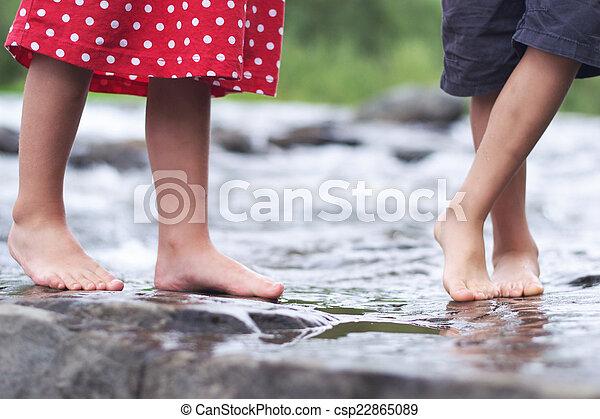 Niños remojando pies en un arroyo - csp22865089