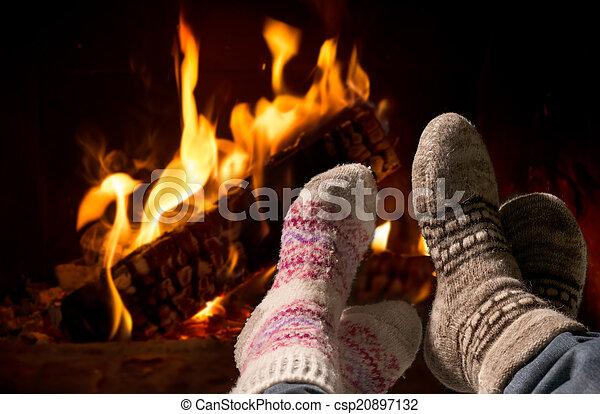 Pies en calcetines de lana calentándose en la chimenea - csp20897132