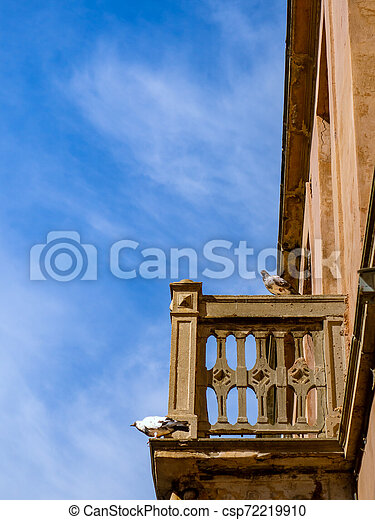 Pigeons standing on the balcony of the old abandoned house - csp72219910
