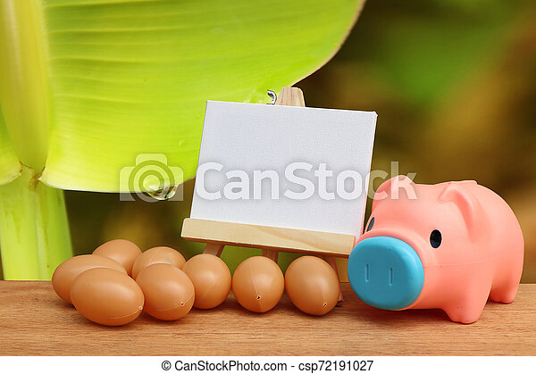 piggy bank and canvas frame with drop from banana stem background - csp72191027