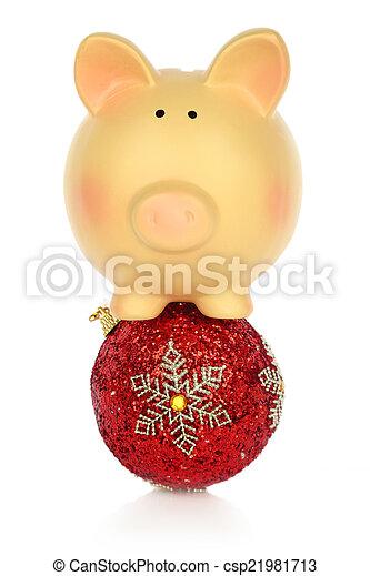 Piggy bank balancing on a Christmas ball - csp21981713
