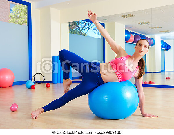 Pilates woman passes fitball exercise workout - csp29969166