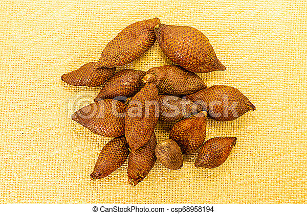 pile fruit brown herring snake fruit Thailand vietnam thin brown rough on a light background - csp68958194