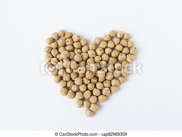 Pile of chickpeas on white background. Garbanzo beans traditional Near Easten food. Heart shape. - csp82969359
