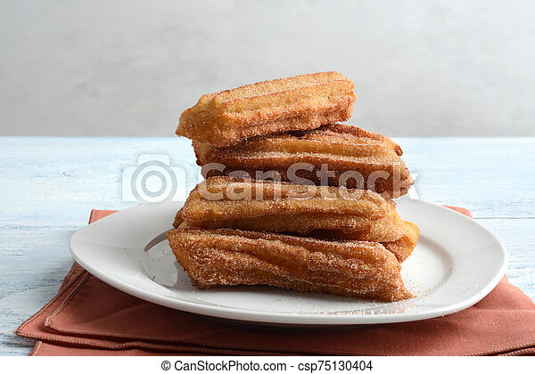Pile of churros on a plate - csp75130404