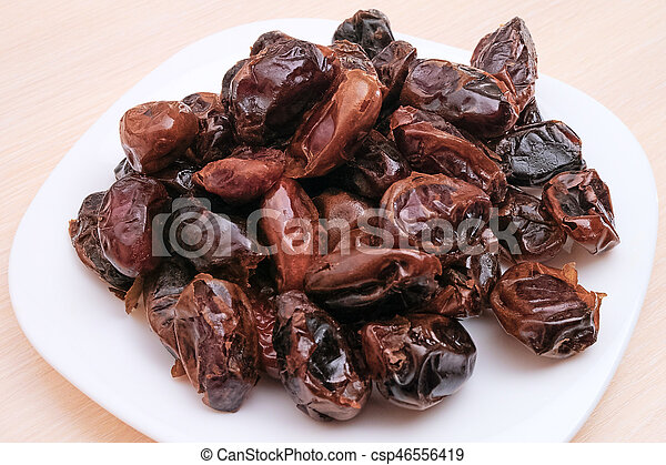 Pile of dates on a white plate - csp46556419