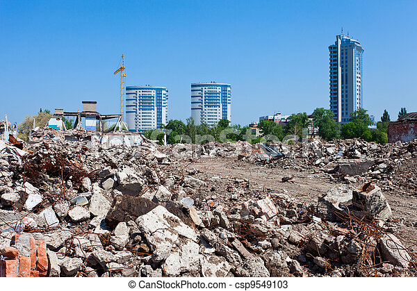 Pile of debris of ruined building on new buildings background  - csp9549103