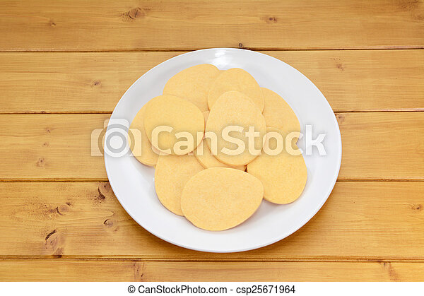 Pile of egg-shaped biscuits on a white plate - csp25671964