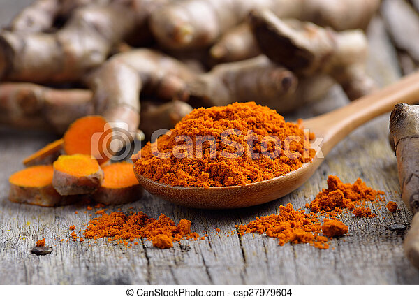 pile of fresh turmeric roots on wooden table - csp27979604