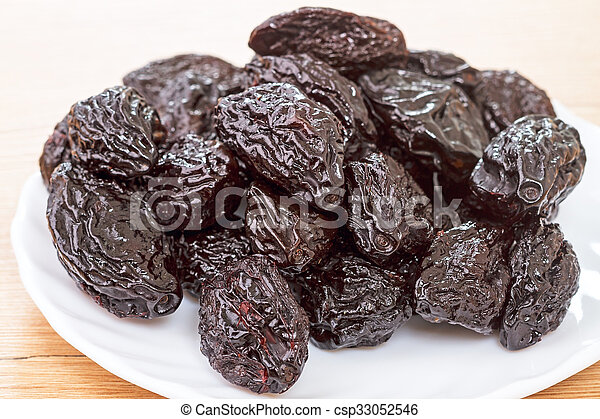 Pile of prunes on a white plate - csp33052546