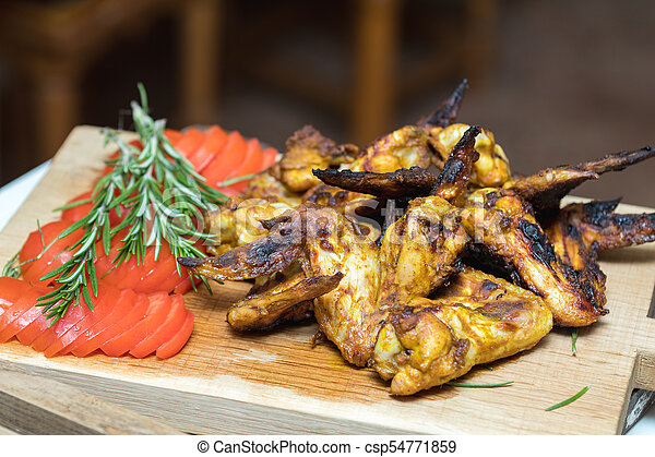 Pile of roasted grilled chicken wings on oak wooden board. - csp54771859
